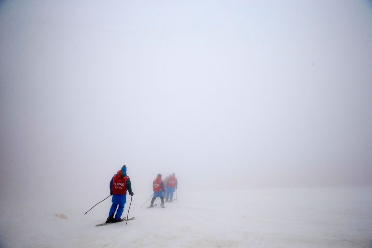 Course slippers make their way down the course as the first race is delayed due to heavy fog during day four of Sochi 2014 Paralympic Winter Games at Rosa Khutor Alpine Center on March 11, 2014 in Sochi, Russia. (Photo by Tom Pennington/Getty Images)