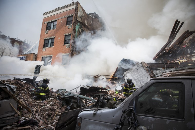 Heavy smoke pours from the debris as the Fire Department of New York (FDNY) responds to a 5-alarm fire and building collapse at 1646 Park Ave in the Harlem neighborhood of Manhattan March 12, 2014 in New York City. Reports of an explosion were heard before the collapse of two multiple-dwelling buildings that left at least 11 injured. (Photo by Andrew Burton/Getty Images)