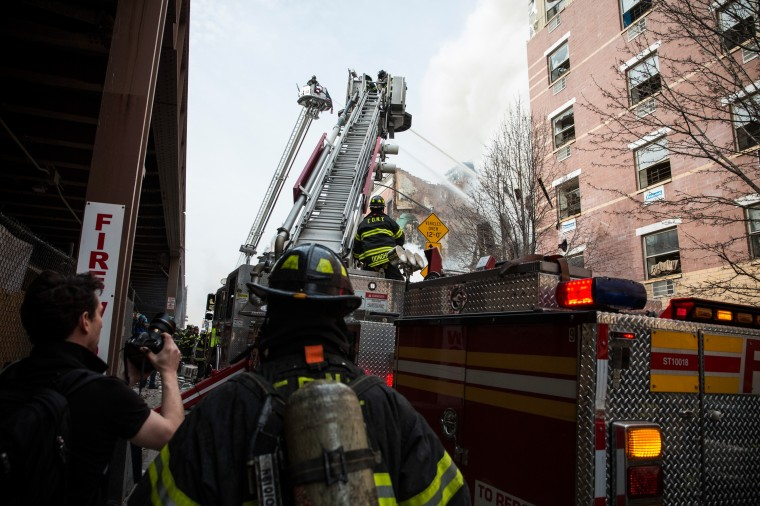 A ladder truck pours water as the Fire Department of New York (FDNY) respond to a 5-alarm fire and building collapse at 1646 Park Ave in the Harlem neighborhood of Manhattan March 12, 2014 in New York City. Reports of an explosion were heard before the collapse of two multiple-dwelling buildings that left at least 11 injured. (Photo by Andrew Burton/Getty Images)