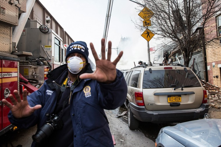 A member of the New York Police Department (NYPD) gestures as as emergency personnel respond to a 5-alarm fire and building collapse at 1646 Park Ave in the Harlem neighborhood of Manhattan March 12, 2014 in New York City. Reports of an explosion were heard before the collapse of two multiple-dwelling buildings that left at least 16 injured. (Photo by Andrew Burton/Getty Images)