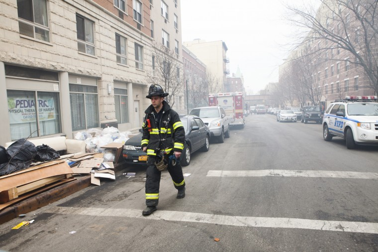 A firefighter near the scene of a gas leak explosion that caused two buildings to collapse on Park Avenue and 116th street in East Harlem in the Harlem neighborhood of Manhattan March 12, 2014 in New York City. Reports of an explosion were heard before the collapse of two multiple-dwelling buildings that left at least 17 injured. (Photo by Christopher Gregory/Getty Images)