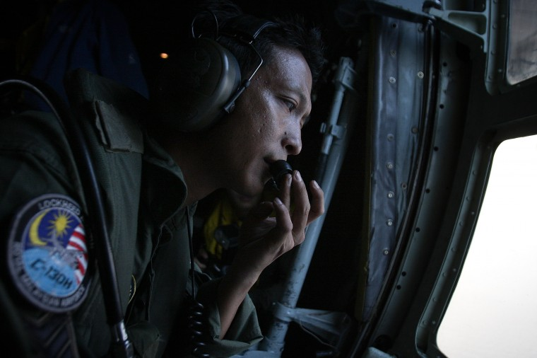 "Sgt. Zulhelmi Hassan of the Malaysian Air Forces communicates with the pilot during a search and rescue mission flight on March 13, 2014 in Kuala Lumpur, Malaysia. A Chinese agency has released a satellite image taken on March 9 of large floating debris in the waters between Kuala Lumpur and South Vietnam, reported to be a ""suspected crash area."" Officials expanded the search area for missing Malaysia Airlines flight MH370 yesterday, beyond the intended flight path to include the west of Malaysia at the Straits of Malacca as new information surfaces about the time Subang air traffic control lost contact with the aircraft. The flight carrying 239 passengers from Kuala Lumpur to Thailand was reported missing on the morning of March 8 after the crew failed to check in as scheduled. (Photo by Rahman Roslan/Getty Images)"