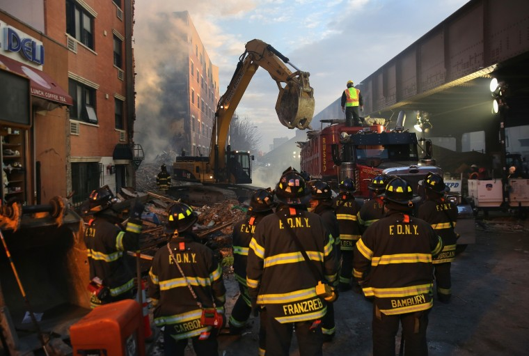 Firemen watch as work crews remove debris from the site of an explosion in East Harlem on March 13, 2014 in New York City. At least 7 people were killed, according to reports, in Wednesday's explosion which collapsed two buildings on Park Avenue at 116th Street. (Photo by John Moore/Getty Images)