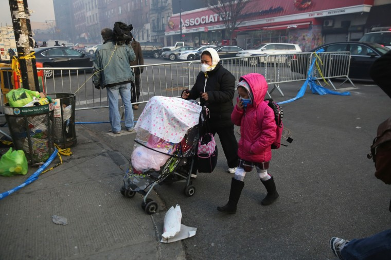 Local residents walk from their homes, wearing protective, near the site of an explosion and building collapse in East Harlem on March 13, 2014 in New York City. At least 7 people were killed, according to reports, in Wednesday's explosion which collapsed two buildings on Park Avenue at 116th Street. (Photo by John Moore/Getty Images)