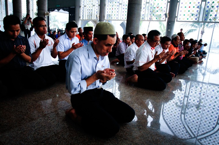 Members of the public, MAS staff, and politicians pray during a special prayer as the search for missing Malaysian airline MH370 expands to the Indian Ocean March 14, 2014 in Kuala Lumpur, Malaysia. The missing aircraft carrying 227 passengers and 12 crew disappeared six days ago baffling the international rescue and search team who have found no remains or clues in the waters surrounding South East Asia. All passengers and crew are currently under investigation for possible sabotage although no evidence of such activity has been found. (Photo by Rahman Roslan/Getty Images)