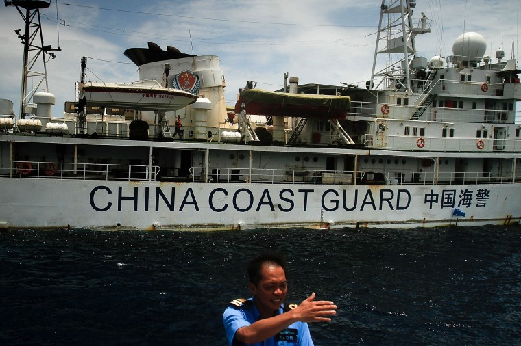 A Malaysian Navy personnel gestures towards the ship's captain as they approach a vessel belonging to the Chinese Coast Guard during an exchange of communication in the South China Sea on March 15, 2014 in Kuantan, Malaysia. During a press conference today the Malaysian Prime Minister, Najib Razak said that investigators had discovered evidence from satellite and radar systems indicating that the communication systems of the aircraft had been intentionally disabled. The search for the plane in the South China Sea has now been abandoned with the focus switching to two flight corridors, the first stretching from the border of Kazakhstan and Turkmenistan to northern Thailand and a second stretching from Indonesia to the South Indian Ocean.The missing aircraft was carrying 227 passengers and 12 crew. (Photo by Rahman Roslan/Getty Images)