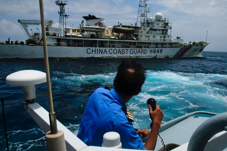 A member of the Malaysian Navy makes a call as their ship approaches a ship belonging to the Chinese Coast Guard during an exchange of communication in the South China Sea on March 15, 2014 in Kuantan, Malaysia. During a press conference today the Malaysian Prime Minister, Najib Razak said that investigators had discovered evidence from satellite and radar systems indicating that the communication systems of the aircraft had been intentionally disabled. The search for the plane in the South China Sea has now been abandoned with the focus switching to two flight corridors, the first stretching from the border of Kazakhstan and Turkmenistan to northern Thailand and a second stretching from Indonesia to the South Indian Ocean.The missing aircraft was carrying 227 passengers and 12 crew. (Photo by Rahman Roslan/Getty Images)