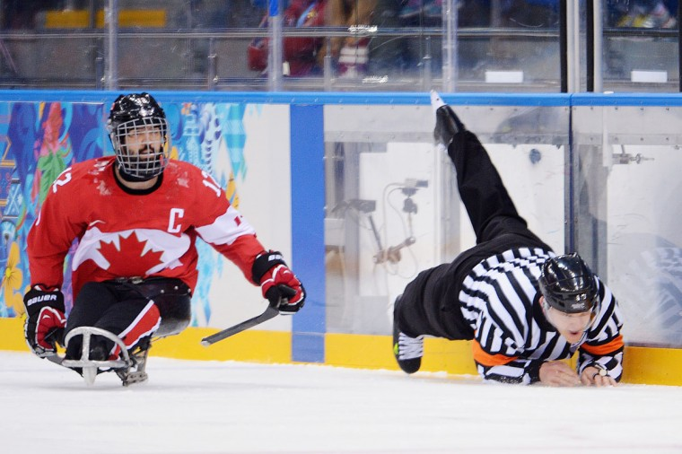 Referee Jonathan Morrsison falls over Greg Westlake of Canada during the Bronze Medal match between Canada and Norway on day eight of the Sochi 2014 Paralympic Winter Games at Shayba Arena on March 15, 2014 in Sochi, Russia. (Photo by Dennis Grombkowski/Getty Images)