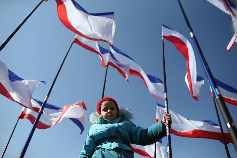 A girl holds a flag during a Pro Russian supporters rally in Lenin Square on March 15, 2014 in Simferopol, Ukraine. As the standoff between the Russian military and Ukrainian forces continues in Ukraine's Crimean peninsula, world leaders are pushing for a diplomatic solution to the escalating situation. Crimean citizens will vote in a referendum tomorrow on whether to become part of the Russian federation. (Photo by Dan Kitwood/Getty Images)