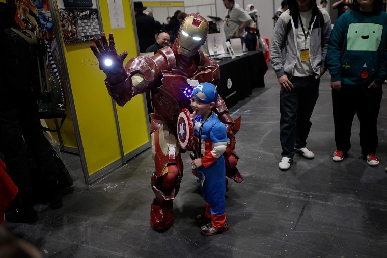 A little boy dressed as Captain America has his photograph taken with the Iron Man as they attend the London Super Comic Convention in the Excel Centre on March 15, 2014 in London, England. Thousands of dedicated fans of comics attended the event this weekend in detailed costumes, paying homage to their most loved superheroes and characters. (Photo by Mary Turner/Getty Images)