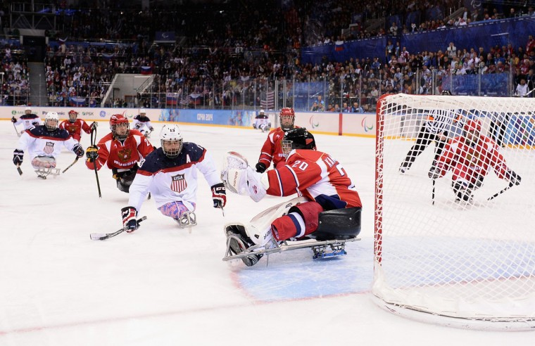 Joshua Sweeney of the United States scores past Vladimir Kamantcev of Russia during the Ice Sledge Hockey Gold Medal game between the United States and Russia on day eight of the Sochi 2014 Paralympic Winter Games at Shayba Arena on March 15, 2014 in Sochi, Russia. (Photo by Dennis Grombkowski/Getty Images)