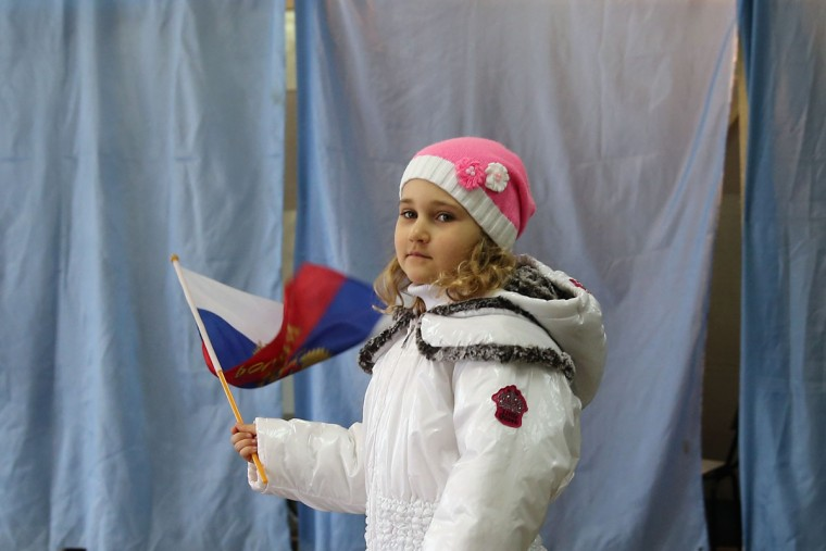 A girl stands outside a polling booth with a Russian flag inside a polling station on March 16, 2014 in Bachchisaray, Ukraine. As the standoff between pro-Russian forces and the Ukrainian military continues in the Crimean peninsula, world leaders are continuing to push for a diplomatic solution to the escalating situation. (Dan Kitwood/Getty Images)