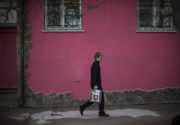 Referendum staff walk on a street as they collect the votes of people too infirm to visit the polling station on March 16, 2014 in a predominantly Russian area of Bachchisaray, Ukraine. (Dan Kitwood/Getty Images)