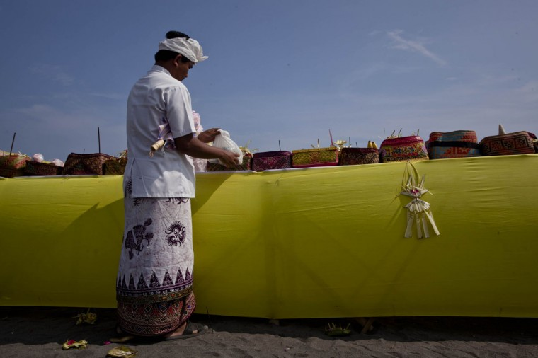 A Hindu devotee puts offerings during the Melasti ritual ceremony at Parangkusumo beach on March 28, 2014 in Yogyakarta, Indonesia. (Photo by Ulet Ifansasti/Getty Images)