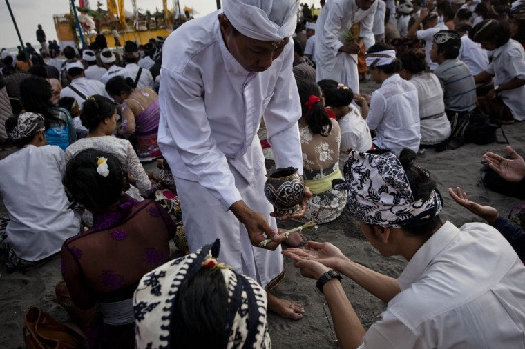 Hindu devotees receive holy water as they pray during the Melasti ritual ceremony at Parangkusumo beach on March 28, 2014 in Yogyakarta, Indonesia. (Photo by Ulet Ifansasti/Getty Images)
