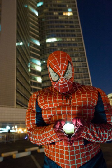 A man dressed in a SpiderMan costume poses with a battery-powered candle in front of the Government of Moscow building as part of the Earth Hour initiative on March 29, 2014 in Moscow, Russia. (Photo by Victor Boyko/Getty Images for Sony)