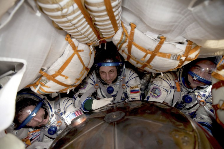 International Space Station (ISS) crew members, US astronaut Dan Burbank, Russian cosmonauts, Anton Shkaplerov and Anatoly Ivanishin, sit inside the Soyuz capsule shortly after the landing in Kazakhstan, near Arkalyk, April 27, 2012. (SERGEI REMEZOV/AFP/GettyImages)