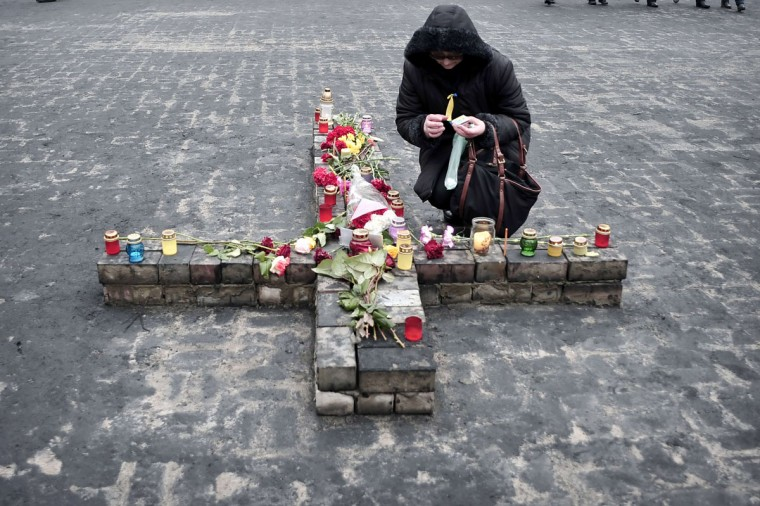 A woman lights a candle at a makeshift memorial in central Kiev on March 2, 2014. (Louisa Gouliamaki/AFP/Getty Images)