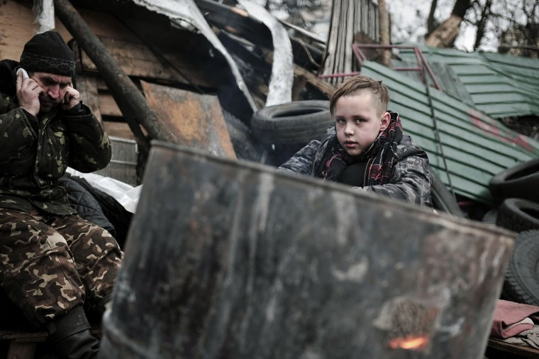 A boy warms near a fire at a barricade in central Kiev on March 2, 2014. Ukraine said Sunday it would call up all military reservists after Russian President Vladimir Putin's threat to invade the country. (Louisa Gouliamaki/AFP/Getty Images)