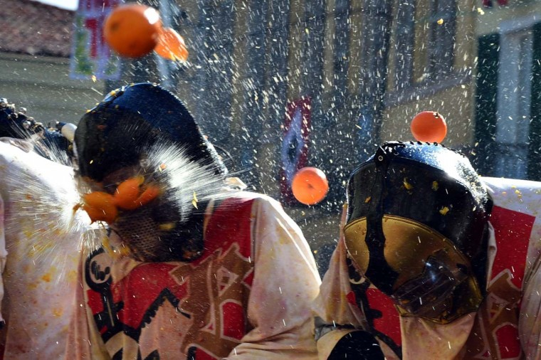 "Men with helmets are hit by oranges during the traditional ""battle of the oranges"" held during the carnival in Ivrea, near Turin, on March 4, 2014. During the event which marks the people's rebellion against tyrannical lords who ruled the town in the Middle Ages, revelers parading on floats represent guards of the tyrant, while those on foot the townsfolk. (Giuseppe Cacace/AFP/Getty Images)"