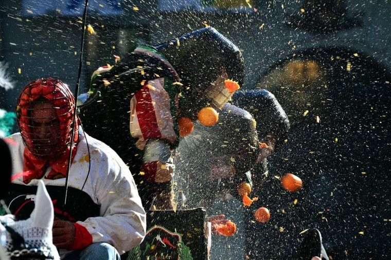 "Men with helmets are hit by oranges during the traditional ""battle of the oranges"" held during the carnival in Ivrea, near Turin, on March 4, 2014. During the event which marks the people's rebellion against tyrannical lords who ruled the town in the Middle Ages, revellers parading on floats represent guards of the tyrant, while those on foot the townsfolk. (Giuseppe Cacace/AFP/Getty Images)"