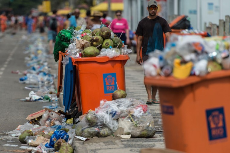 People walk by full trash cans on Ipanema beach, during a strike by some garbage collectors in Rio de Janeiro, Brazil on March 6, 2014. (YASUYOSHI CHIBA/AFP/Getty Images)