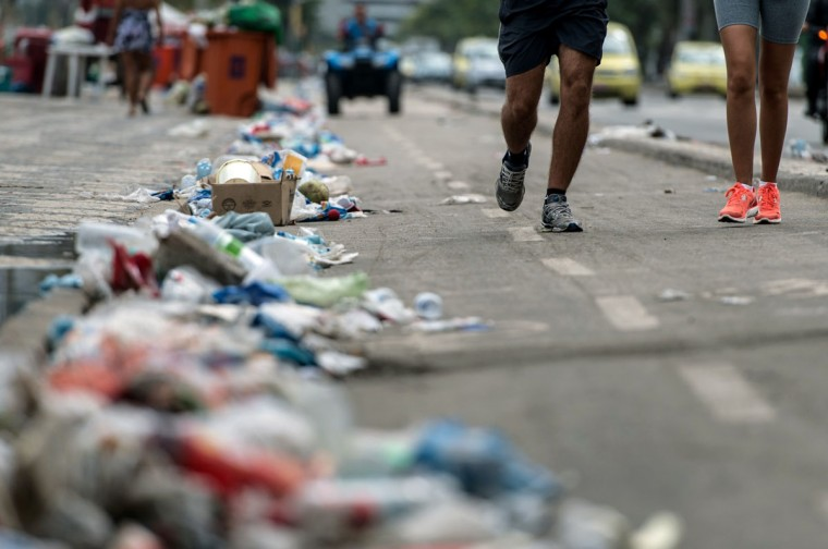 People run next to piled garbage during a strike by some garbage collectors in Rio de Janeiro, Brazil on March 6, 2014. (YASUYOSHI CHIBA/AFP/Getty Images)