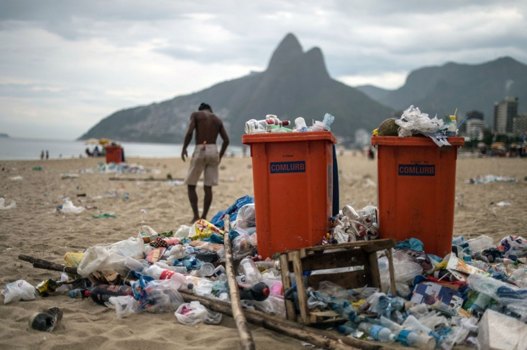 A man walks next to full trash cans on Ipanema beach during a strike by some garbage collectors in Rio de Janeiro, Brazil on March 6, 2014. (YASUYOSHI CHIBA/AFP/Getty Images)