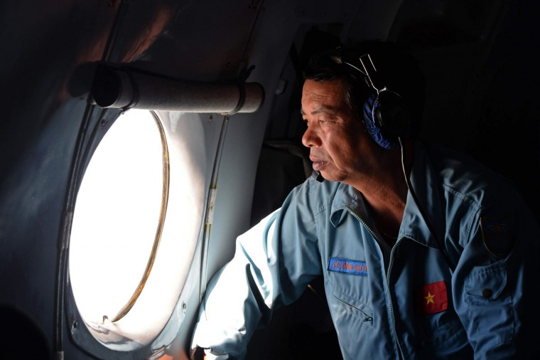 This aerial picture, taken aboard a Soviet-made AN-26 used as a search aircraft by the Vietnamese Air Force to look for missing Malaysia Airlines flight MH370, shows an Air Force officer looking out a window over the southern seas off Vietnam on March 9, 2014. (Hoang Dinh Nam/AFP/Getty Images ORG)
