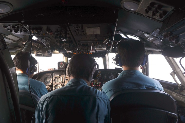 This picture, taken from aboard a flying Soviet-made AN-26 used as a search aircraft by the Vietnamese Air Force to look for missing Malaysia Airlines flight MH370, shows crew members in the cockpit during search operations over the southern seas off Vietnam on March 9, 2014. (Hoang Dinh Nam/AFP/Getty Images)