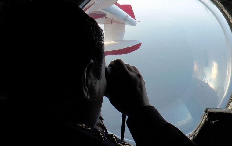 Malaysian Maritime Enforcement personnel look through binoculars during search and rescue operations for the missing Malaysia Airlines Boeing 777-200 as they fly over the waters off the northeastern coast of peninsula Malaysia. (Malaysian Maritime Enforcement handout photo/AFP/Getty Images)