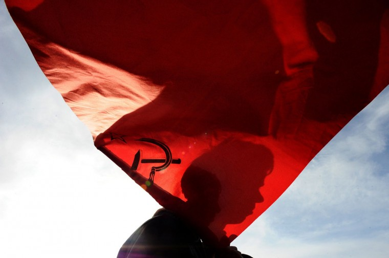 "The silhouette of a man's face is seen on a Soviet Union flag during a rally in St. Petersburg to show support for pro-Russian authorities in the Ukrainian region of Crimea on March 9, 2014. Russia's incursion in Crimea is a ""serious miscalculation"" and Moscow could face far-reaching economic consequences unless a diplomatic solution can be found, British Foreign Secretary William Hague said on March 9. (Olga Maltseva/AFP/Getty Images)"