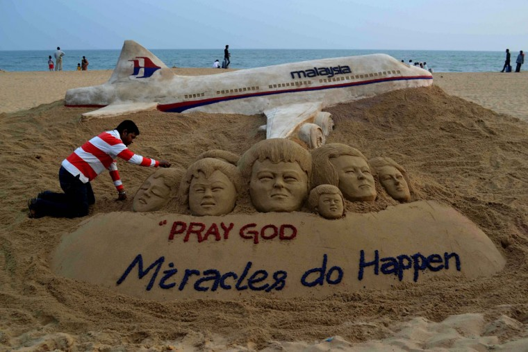 Indian sand artist Sudersan Pattnaik gives final touches on a sand sculpture at Puri Beach in India with a message of prayers for the missing Malaysia Airlines flight MH370, which vanished from radar early on March 8 somewhere at sea between Malaysia and Vietnam. (Asit Kumar/AFP/Getty Images)