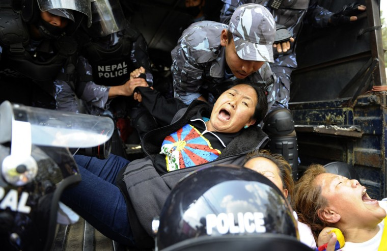 Nepalese riot police arrest Tibetan protesters in front of the consular section of the Chinese Embassy in Kathmandu on March 10, 2014, during a protest marking the 55th anniversary of the 1959 Tibetan uprising against Chinese rule. (PRAKASH MATHEMA/AFP/Getty Images)