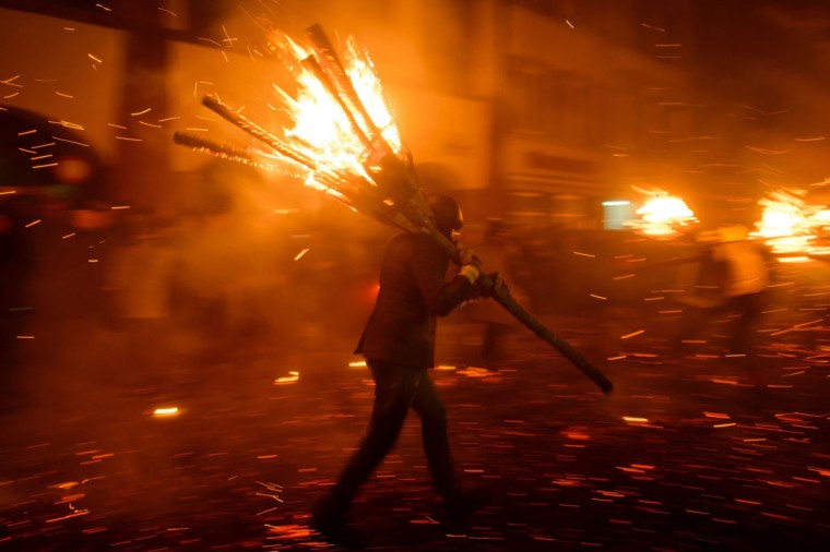 "A reveller carries a ""Chienbaese"", made of burning bundles of pinewood chips, during the traditional Swiss ""Chienbaese"" celebration on March 9, 2014 in the streets of Liestal, near Basel. (FABRICE COFFRINI/AFP/Getty Images)"