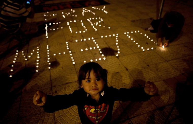 A Malaysian child reacts to the camera as others light candles during a vigil for missing Malaysia Airlines passengers at the Independence Square in Kuala Lumpur on March 10, 2014. (MANAN VATSYAYANA/AFP/Getty Images)