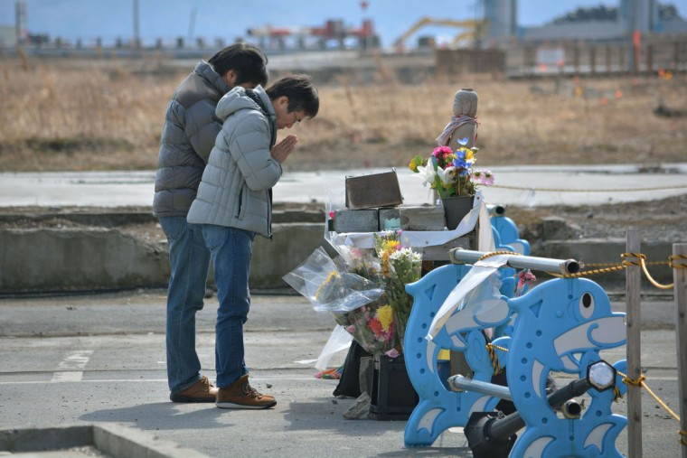 People pray for victims of the massive earthquake and tsunami at the former disaster control center in Minamisanriku, Miyagi prefecture on March 9, 2014, two days before the third anniversary of the March 11, 2011 earthquake and tsunami. The 9.0 magnitude earthquake in 2011 sent a huge wall of water into the coast of the Tohoku region, splintering whole communities, ruining swathes of prime farmland and killing nearly 19,000 people. (KAZUHIRO NOGI/AFP/Getty Images)