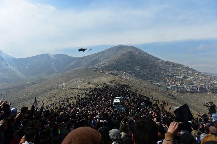 A helicopter flies over Afghan residents as they attend the burial of Afghan Vice-President Marshal Mohammad Qasim Fahim, formerly one of the country's most feared warlords, at a ceremony on a hilltop in Kabul on March 11, 2014. Afghan Vice-President Marshal Mohammad Qasim Fahim died of natural causes after a turbulent life that reflected the country's recent past. Fahim, a leader of the Tajik ethnic minority, was senior vice-president under President Hamid Karzai, who will step down at elections next month as US-led combat forces pull out of Afghanistan after 13 years of fighting the Taliban. (Wakil Kohsar/AFP/Getty Images)