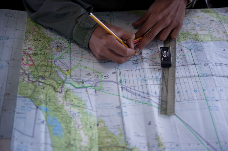 Royal Malaysian Air Force Navigator captain, Izam Fareq Hassan marks locations on a map onboard a Malaysian Air Force CN235 aircraft during a search and rescue (SAR) operation to find the missing Malaysia Airlines flight MH370 plane over the Strait of Malacca on March 14, 2014. Malaysia confirmed on March 14 that the search for a missing Malaysia Airlines plane had been expanded into the Indian Ocean, but declined to comment on US reports that the jet had flown for hours after going missing. (Mohd Rasfan/AFP/Getty Images)