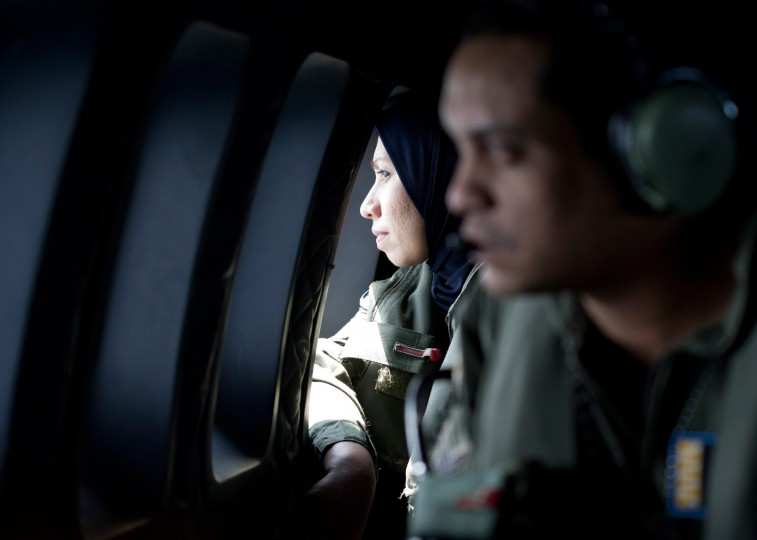Crew members look outside windows from a Malaysian Air Force CN235 aircraft during a search and rescue (SAR) operation to find the missing Malaysia Airlines flight MH370 plane over the Strait of Malacca on March 14, 2014. Malaysia confirmed on March 14 that the search for a missing Malaysia Airlines plane had been expanded into the Indian Ocean, but declined to comment on US reports that the jet had flown for hours after going missing. (Mohd Rasfan/AFP/Getty Images)