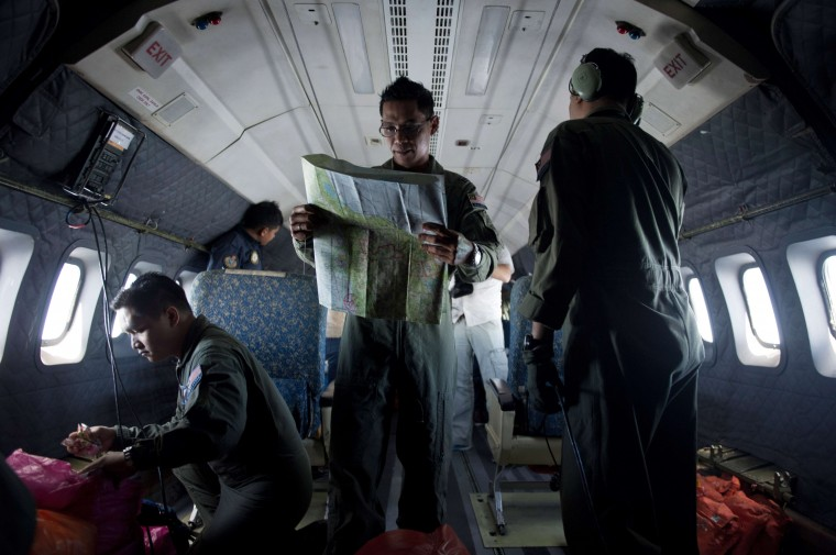 A Royal Malaysian Air Force Navigator captain, Izam Fareq Hassan (C) looks at a map onboard a Malaysian Air Force CN235 aircraft during a search and rescue (SAR) operation to find the missing Malaysia Airlines flight MH370 plane over the Strait of Malacca on March 14, 2014. Malaysia confirmed on March 14 that the search for a missing Malaysia Airlines plane had been expanded into the Indian Ocean, but declined to comment on US reports that the jet had flown for hours after going missing. (Mohd Rasfan/AFP/Getty Images)