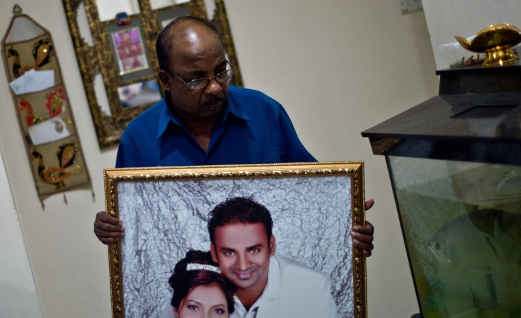 In this picture taken on March 14, 2014, Subramaniam Gurusamy, 60, shows a portrait of his son Puspanathan who was onboard the missing Malaysia Airlines MH370 flight at his home in Teluk Panglima Garang, outside Kuala Lumpur. Malaysian Prime Minister Najib Razak said that Malaysia was ending a search in the South China Sea for a vanished jetliner after investigations indicated the missing plane likely turned far to the west. (Mahah Vatsyayana/AFP/Getty Images)