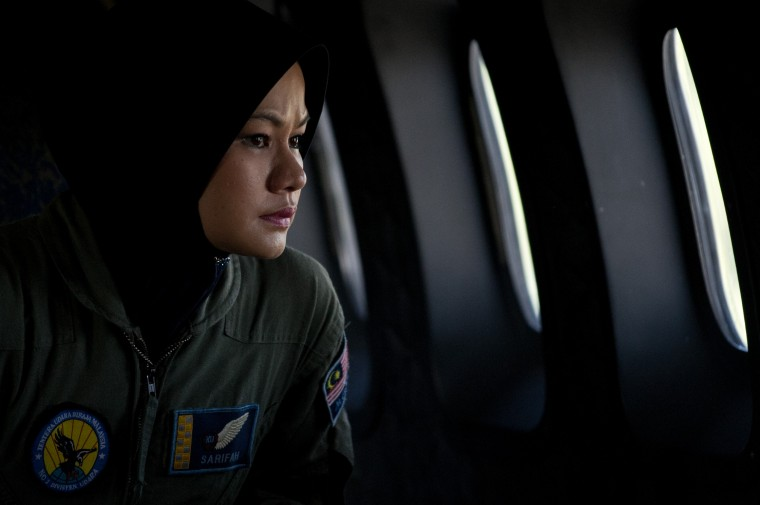 A crew member looks out the windows from a Malaysian Air Force CN235 aircraft during a search and rescue (SAR) operation to find the missing Malaysia Airlines flight MH370 plane over the Strait of Malacca on March 15, 2014. Prime Minister Najib Razak said on March 15 that Malaysia was ending a search in the South China Sea for a vanished jetliner after investigations indicated the missing plane likely turned far to the west. (Mohd Rasfan/AFP/Getty Images)