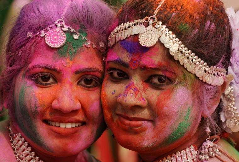 Indian revelers covered with colored powder pose for a photograph during celebrations for the Holi festival in Siliguri on March 16, 2014. Holi is a popular Hindu spring festival observed in India and Nepal at the end of winter season on the last full moon day of the lunar month. (Diptendu Dutta/AFP/Getty Images)