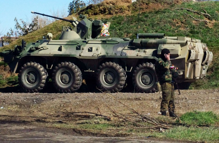 A Russian troop stands guard in front of an APC at a checkpoint in Crimea, near the town of Armyansk, Ukraine, on March 16, 2014. Crimea has been seized by Russian forces over the past month after Ukraine's uprising, plunging US-Russia ties to their lowest point since the fall of the Berlin Wall in 1989. (Alexey Kravtsov/AFP/Getty Images)