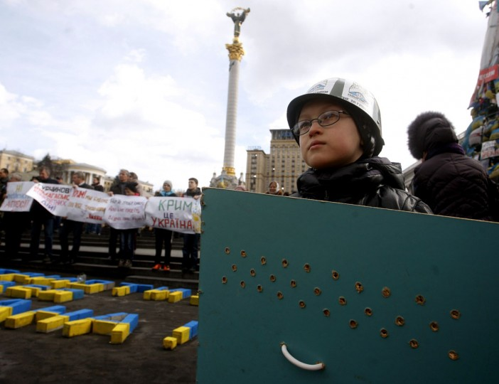 A boy, wearing a toy helmet, holds a shield, similar to the ones' used by Maidan Square activists, at Independence Square in Kiev on March 16, 2014, during a rally to support Crimea's status as part of Ukraine. Crimeans voted on March 16 in a unique referendum on breaking away from Ukraine to join Russia. (Yury Kirnichny/AFP/Getty Images)