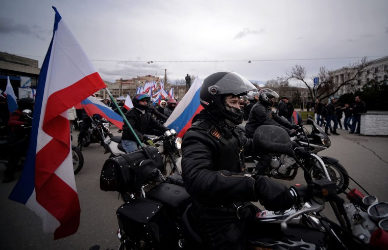 Motorcyclists bearing the Russian and Crimean flags pass by Simferopol's Lenin Square on March 16, 2014. (Filippo Monteforte/AFP/Getty Images)