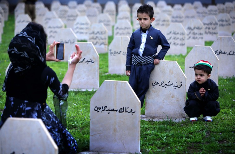 An Iraqi Kurd family visits a graveyard for the victims of a gas attack by former Iraqi president Saddam Hussein in 1988, as people mark the 26th anniversary of the attack in the Kurdish town of Halabja, 300 kms (190 miles) northeast of Baghdad on March 16, 2014. Some 5,000 civilians, mostly women and children, were killed in the chemical gas attack by Saddam Hussein's air force as part of a campaign to crush a Kurdish rebellion, Kurdistan Region President Masoud Barzani today, signed a regional directive to promote Halabja from district status to a province. (Safin Hamed/AFP/Getty Images)