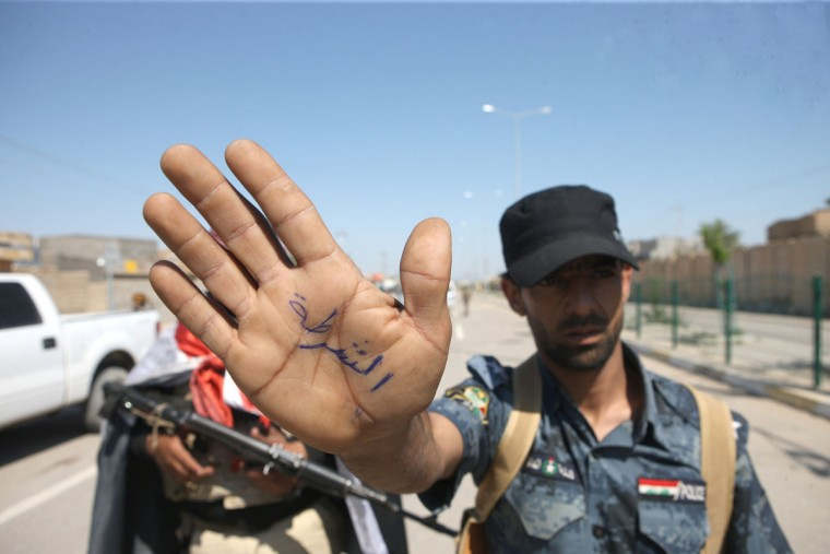 "An Iraqi policeman shows the palm of his hand with the word ""police"" written on it after the southern districts of the city of Ramadi, the capital of the Anbar province, were recaptured by government forces from militants, on March 16, 2014. Anbar has been roiled in recent months by unrest that has seen anti-government fighters take control of the mainly Sunni Muslim city of Fallujah in the Anbar province, as well as shifting areas of the city of Ramadi, west of the Iraqi capital Baghdad. (Azhar Shallal/AFP/Getty Images)"