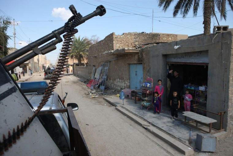 Iraqis stand looking at a security forces convoy that patrols a street after local police took control of the Southern area of the city of Ramadi, west of the capital Baghdad in the Anbar province, on March 16, 2014. (Azher Shallal/AFP/Getty Images)